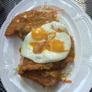 Pork schnitzel with coleslaw, poppy seed dressing, Carolina barbeque & fried eggs